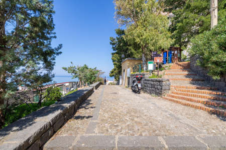 Cefalu, Italy - March 24, 2019: Entrance to Rocca di Cefalù, stairs leading to the pathway to hill top with the sea in the background in Sicily. 新聞圖片