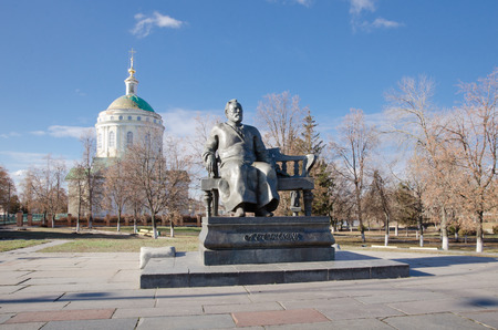 godly: ORYOL, RUSSIA - November 02, 2014: Monument to great Russian writer Nikolai Semenovich Leskov and orthodox church. Stock Photo