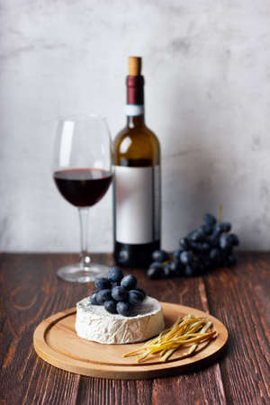 Cheese plate served with red wine and grape. Assorted cheeses Camembert and smoke cheese. Imagens