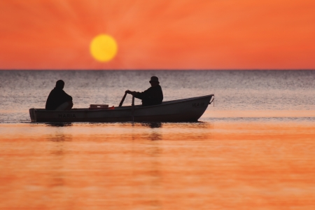Two silhouettes of men in a fishing boat at sunset photo