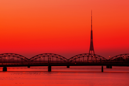 Riga Radio and TV Tower with famous railway bridge at sunset