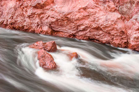 granite park: Flowing water around red stones in Lapland. Long exposure to get blurry water. Stock Photo