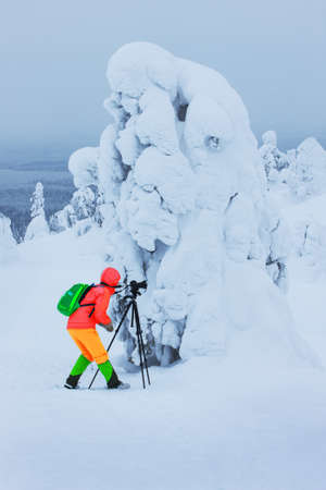 Photographer shooting a picturesque Lapland winter landscape photo