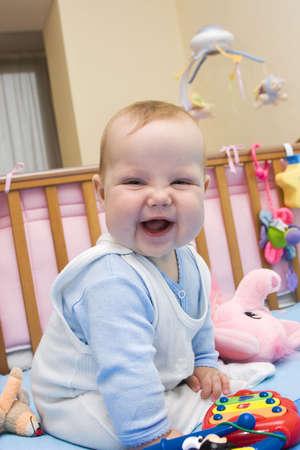 Smiling baby sitting among toys