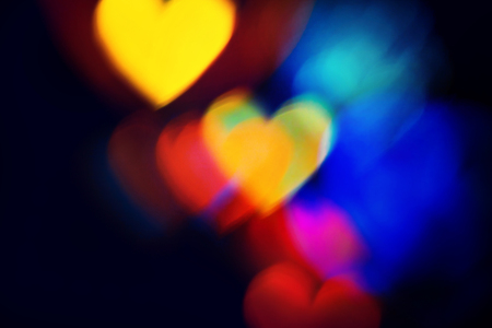 Blurred Colourful heart shapes bokeh sparse on dark background. For Christmas and Valentines day greeting cards, invitations, flyers, perfect for blog posts, banners and social networks