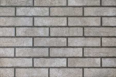 Closeup of modern neutral grey brick wall with dark seams. For pattern, texture and background