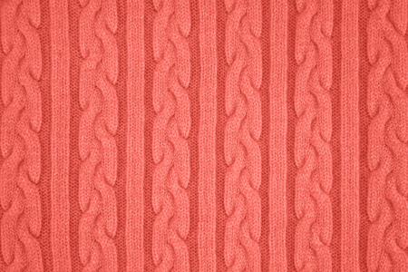 Trendy coral colored Knitwear Fabric Texture with Pigtails and stripes. Repeating Machine Knitting Texture of Sweater. Knitted Background. Color of the year 2019 写真素材