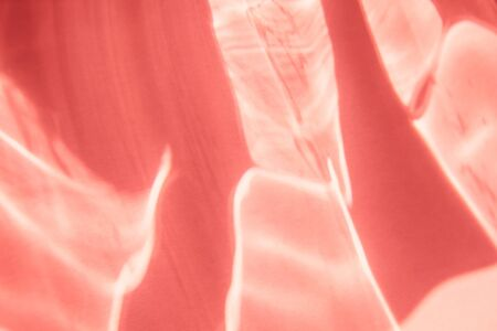 Trendy coral colored abstract background with light and shadows caustic effect. Light passes through a glass.
