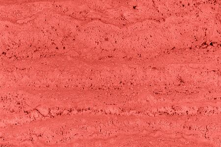 Closeup of trendy coral colored porous stone textured wall. Abstract color nature background for design and skins.