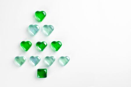 Christmas tree made of green and clear decorative glass hearts laying on white background. MInimal flat lay New Year holiday concept. Stock Photo