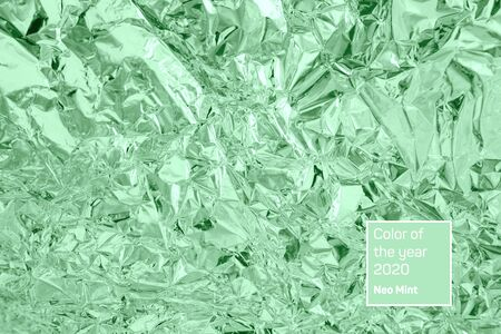 Abstract trendy mint colored crumpled foil texture background. Color trend concept.