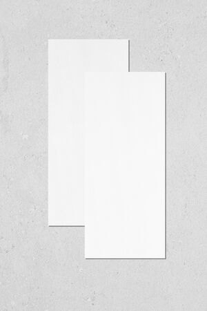Two empty white vertical rectangle price-list or menu mock ups with soft shadows lying on top of each other on neutral light grey concrete wall background. Flat lay, top view