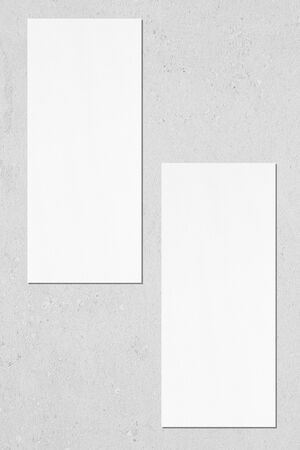 Two empty white vertical rectangle price-list or menu mock ups with soft shadows lying on neutral light grey concrete wall background. Flat lay, top view
