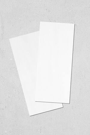 Two empty white vertical rectangle price-list or menu mock ups with soft shadows lying diagonally on top of each other on neutral light grey concrete wall background. Flat lay, top view