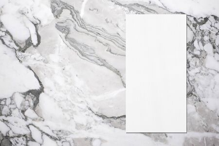 Empty white vertical rectangle price-list or menu mock up with soft shadows on grey marble background. Flat lay, top view. Copy space for text. Stockfoto