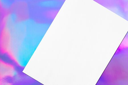 Close up of empty white rectangle poster mock up lying diagonally with soft shadow on holographic background. Flat lay, top view. Open composition.
