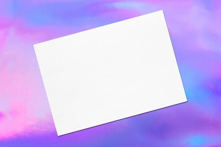 Empty white horizontal rectangle poster mock up with soft shadow lying diagonally on holographic background. Flat lay, top view