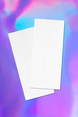 Two empty price-list or menu mock ups lying diagonally on top of each other with soft shadows on holographic background. Flat lay, top view