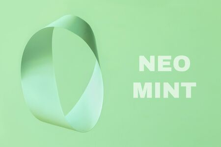 Mobius strip made from paper soaring in the air on mint background. Trendy surreal airy image. Abstract color concept.