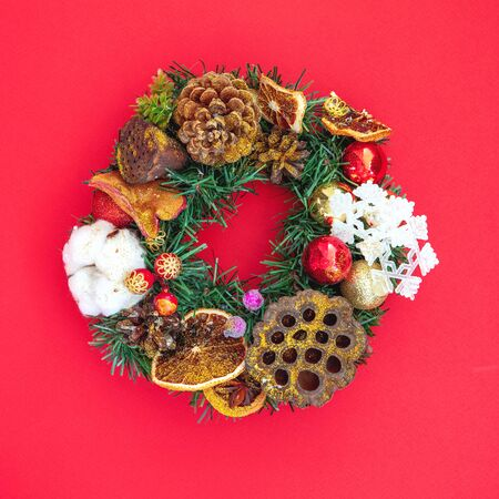 Beautiful Decorative Christmas wreath on red background. Top view, flat lay style.
