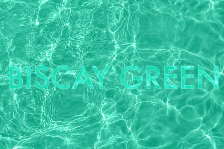 Trendy transparent mint colored text on calm clear water surface. Color trend concept.