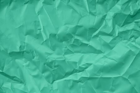Trendy mint colored textured background. Crumpled satin paper texture. Flat lay. Year color concept.
