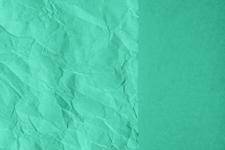 Crumpled and plain paper sheets divided creating line partition. Trendy mint colored abstract background design. Flat lay, copy space. Year color concept.