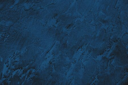 Dark blue colored low contrast stone textured background with roughness and irregularities to your design or product. Color trend concept.