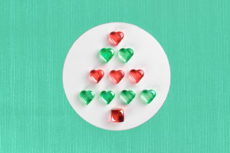 Christmas tree made of red and green decorative glass hearts laying in white circle on striped textured trendy mint background. Minimal flat lay New Year holiday concept. Banco de Imagens