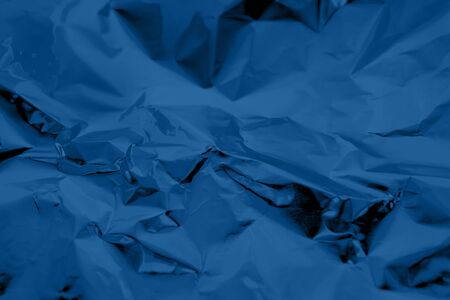 Abstract trendy dark blue colored crumpled foil texture background. 2020 color trend concept.