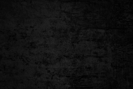 Black low contrast concrete textured wall background with roughness and irregularities to your concept or product.