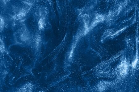 Abstract elegant, detailed blue glitter particles flow with shallow depth of field underwater. Holiday magic shimmering luxury background. Festive sparkles. de-focused