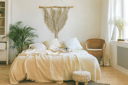 Modern romantic scandi boho style bedroom interior with decorative pillows, green plant and diy macrame wall panel. Light warm cozy comfortable home. jomo, weekend breakfast in bed concept.
