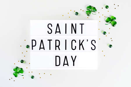Lightbox with Saint Patricks day text and shamrocks made of green glass hearts