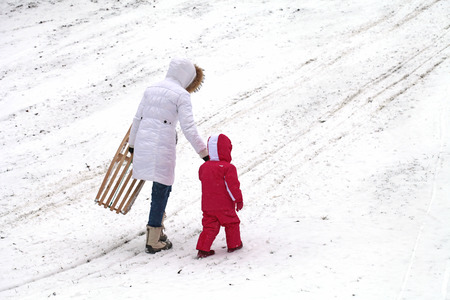 Mother and daughter sledding at winter photo