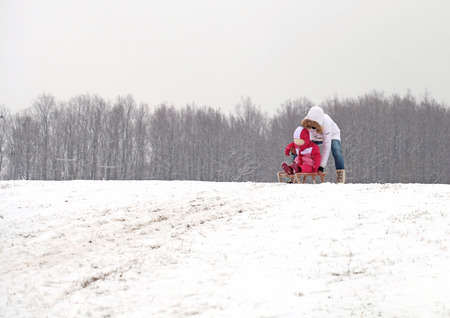 Mother and daughter sledding at winter Stock Photo - 25945536