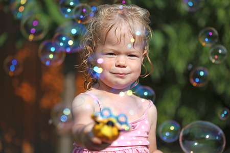 int: Happy little girl playing with soap bubbles int he garden Stock Photo