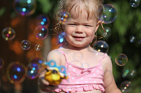 Happy little girl playing with soap bubbles int he garden Zdjęcie Seryjne