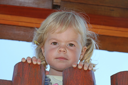 Portrait of cute blond girl holding on to wooden fence.