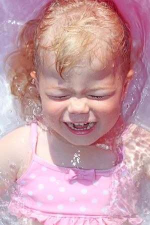 Little blonde girl in the water in summer