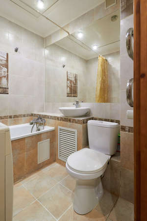 Photo of a small toilet room with a toilet, a bathtub and a mirror