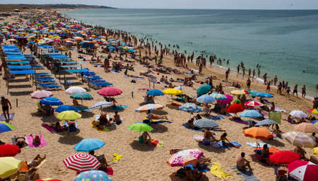 Crowded beach in summer on Algarve Coastline, Portugal Editorial