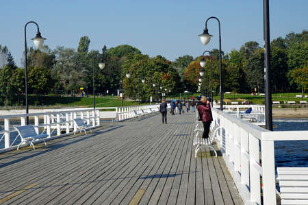 Gdynia Orlowo, Poland, September 30, 2017: people walking along the pier on sunny day.