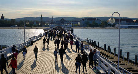 SOPOT, POLAND: SEPTEMBER 30, 2017: Tourists walking on the wooden pier on September 30, 2017 in Sopot, Poland.