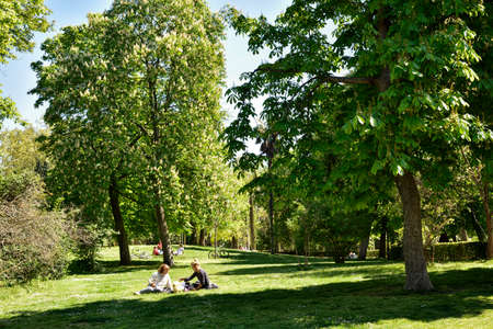 MADRID / SPAIN - APRIL 12, 2019 - Family sitting under beautiful tree in the public Gardens of the Good Retreat (Jardines del Buen Retiro). Stock Photo - 137014174
