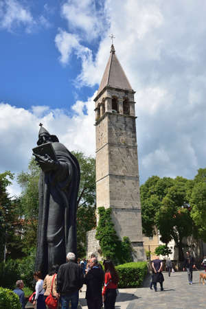 SPLIT, CROATIA - APRIL 29, 2019: Monumental bronze statue of Bishop Gregory of Nin created in 1929 by Ivan Mestrovic and The bell tower and the Chapel of the Holy Arnir Editorial
