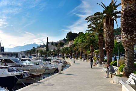 BRELA, CROATIA - MAY 3, 2019 - The boardwalk in the harbor at Brela. The Makarska riviera in Croatia is famous for its beautiful pebbly beaches and crystal clear water. Editorial