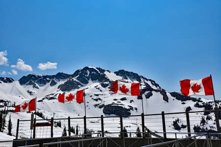 WHISTLER, BC, CANADA, MAY 30, 2019: The Canadian flags on the top of Blackcomb mountain in Whistler Village. Whistler is a canadian resort town visited by over 2 million people annually.