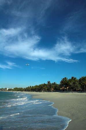 a plane over a caribbean beach photo