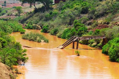 Un pont détruit traversant une rivière sale